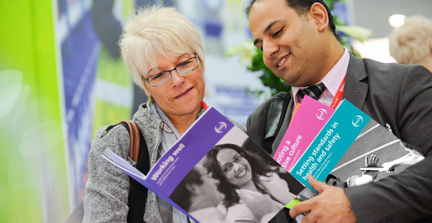 A woman and a man reading through a selection of IOSH advice guides at a conference