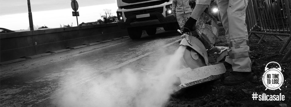 Worker cutting the road surface with a circular saw and producing dust